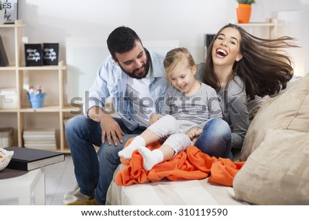Mom dad and daughter playing in the living room - stock photo