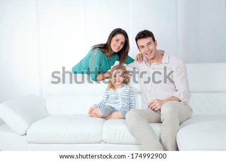 mom dad and daughter sitting on the sofa - stock photo