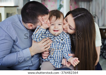 Mom, dad, and daughter. The girl laughs. - stock photo