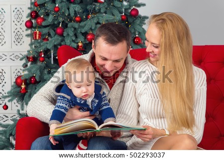 Mom, dad and their little son reading together tales of near a Christmas tree. Happy Family - New Year's holidays.