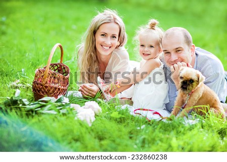 Mom, dad, little girl blonde and dog lie together on the grass and laugh happily - stock photo
