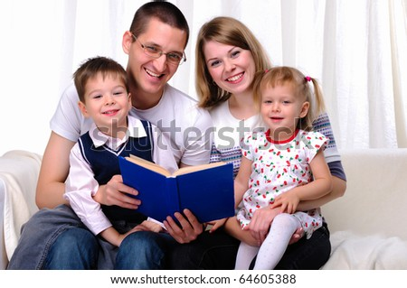 Mom, daughter, son and dad reading a book together on the couch - stock photo