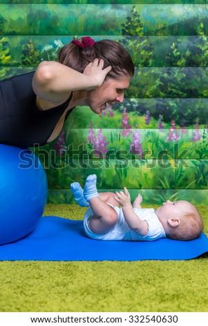Mom does gymnastics with the child. Fun mood. Blue ball for gymnastics. - stock photo