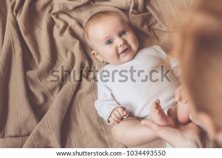 mom dresses the baby on the bed at the day time