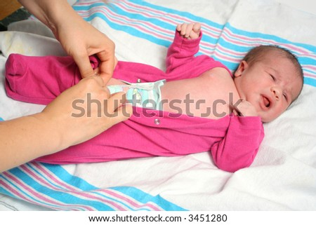 mom dresses up a newborn baby girl in a sleeper - stock photo