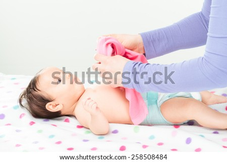 Mom dressing her little baby girl. Copy space above - stock photo