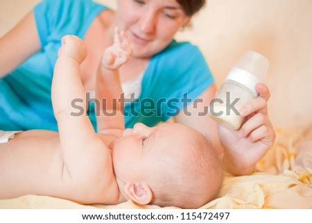 Mom  feed  baby with bottle, play in bed