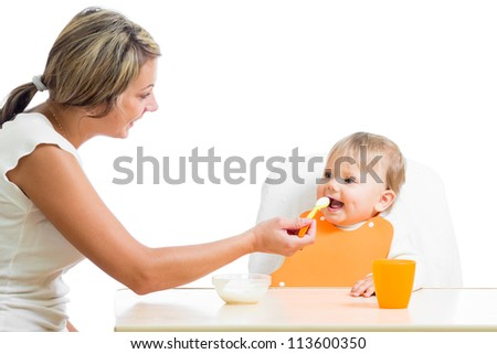 mom feeding her happy baby girl by spoon - stock photo
