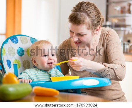 Mom feeds baby boy with spoon