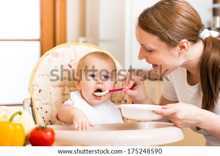 Mom feeds baby with spoon