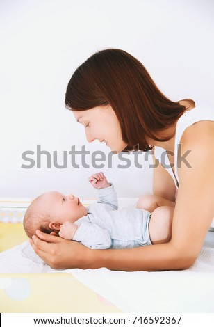 Mom gently care of baby on changing table at home. Beautiful young mother and smiling cutest newborn child. Baby caring routine.