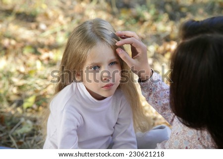 Mom gently stroking her daughter's head sitting in autumn park