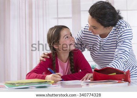 Mom helping her daughter do homework - stock photo