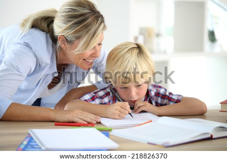 Mom helping little boy to do homework - stock photo