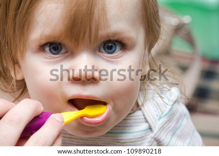 mom helping out a little girl with a toothbrush - stock photo
