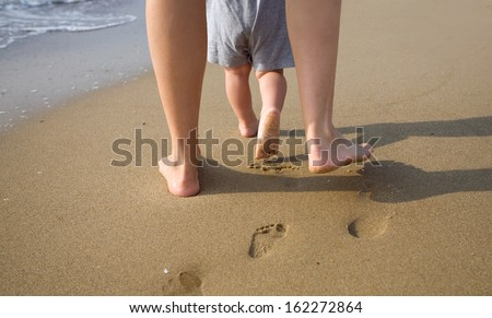 mom helps to make the child's first steps on the beach - stock photo