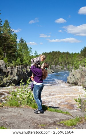 Mom holding baby daughter in her arms near a waterfall at summer season - stock photo