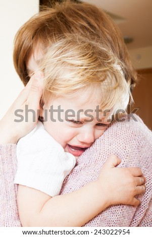 Mom holding  crying child in your arms - stock photo