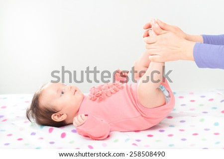Mom holding her little daughter's feet. Copy space above - stock photo