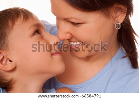 mom holding her smiling son on a white background