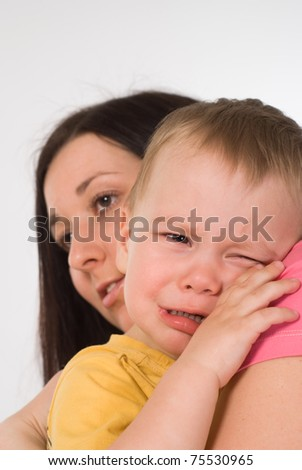 mom holds a crying baby on a white background