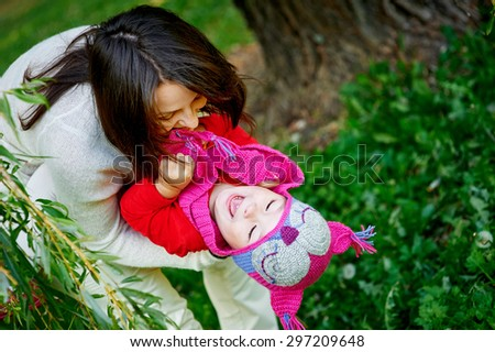 Mom holds daughter on hands in park - stock photo