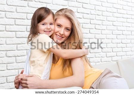 Mom, hugging, sofa. - stock photo