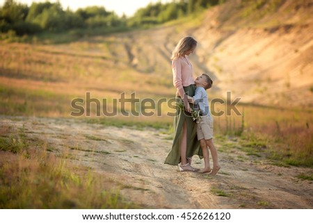 mom in a beautiful green skirt and pink blouse hugs her son looking at each other tenderly in the field with flowers - stock photo