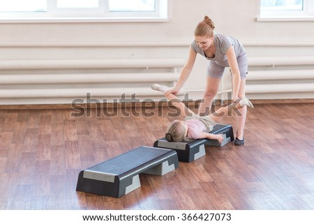 Mom is doing exercises gymnastics coach with a daughter in the gym.