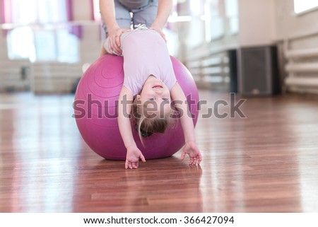 Mom is doing exercises gymnastics coach with a daughter in the gym. - stock photo