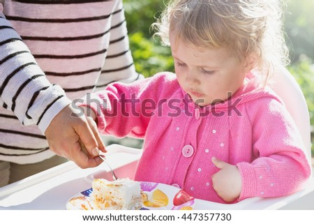 Mom is feeding her daughter at a children's birthday party. Outdoors. Holidays and events. - stock photo