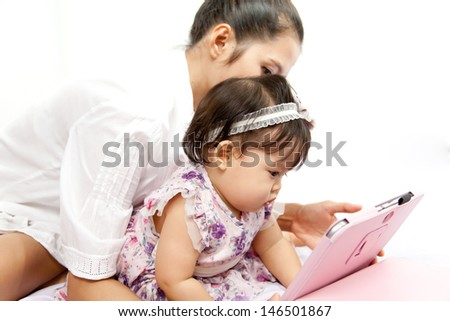 Mom is playing tablet with her baby