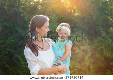 Mom keeps daughter in her arms and plays on the nature. - stock photo