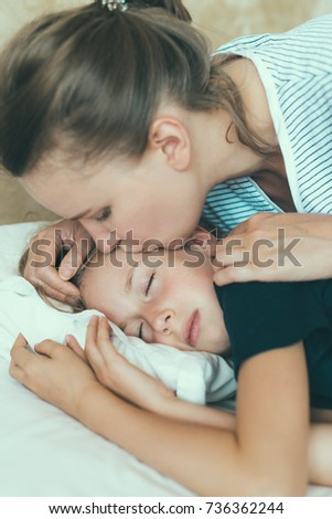 Mom kisses her daughter before going to bed.