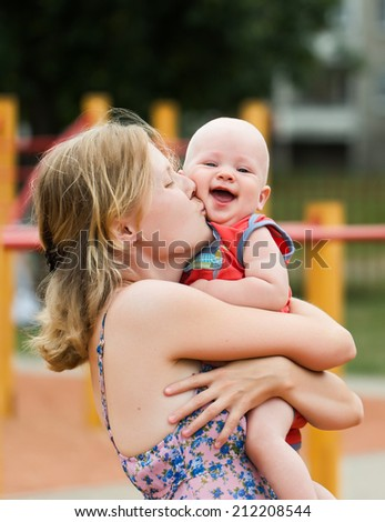 Mom kissing baby in the park - stock photo