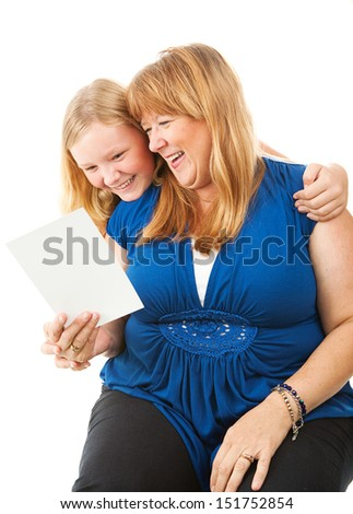 Mom laughs as she reads a greeting card from her daughter.  Mother's Day or birthday concept.  Isolated on white.   - stock photo