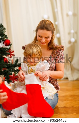 Mom looking with daughter inside of Christmas socks near Christmas tree