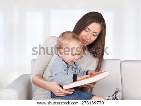 Mom. Mother reading a book a little baby daughter on the sofa at home - stock photo