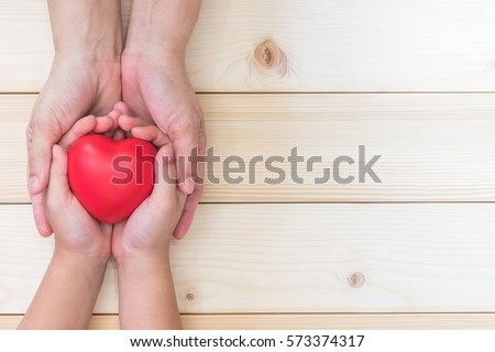 Mom Mother's hand holding daughter, son child kid palm supporting red heart love ball on light white wood background: Nursing children home day care health care concept: Hospital medical business