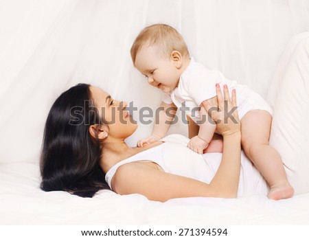 Mom playing with her baby and having fun at home on the bed - stock photo