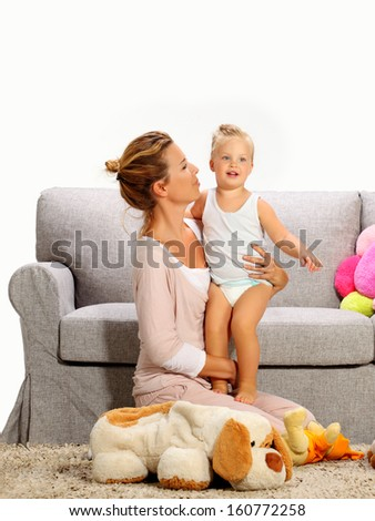 mom  playing with his daughter on the carpet in the living room - stock photo