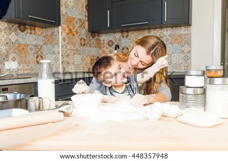 Mom playing with kid in the kitchen. Kitchen is done is dark colors and rustic style. Kid is covered in flour and points to his left with finger. Table is made from light wood.  - stock photo