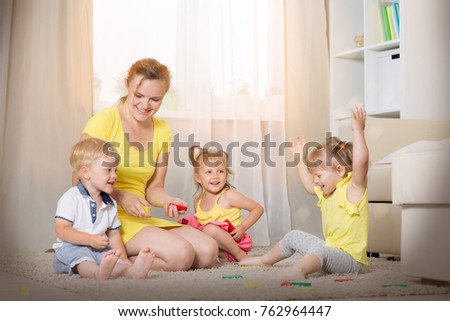 Mom plays with children twins in the room