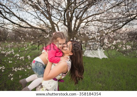 Mom plays with her daughter in the lush spring garden, smiling, family, love - stock photo