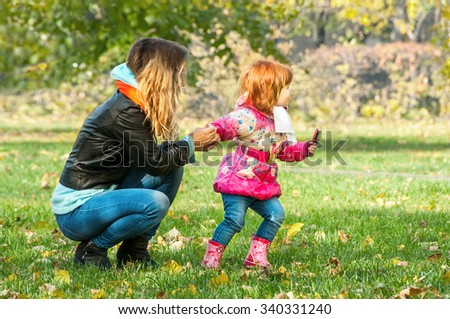 Mom plays with her daughter in the park - stock photo