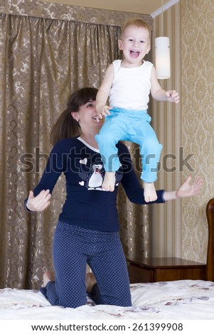Mom plays with her son in a bedroom and throws it - stock photo
