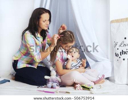 Mom plays with two daughters. The concept of family and lifestyle.