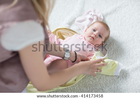 Mom puts clothes on the baby. Woman puts her baby. - stock photo