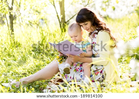 mom reading a book to baby outdoors - stock photo