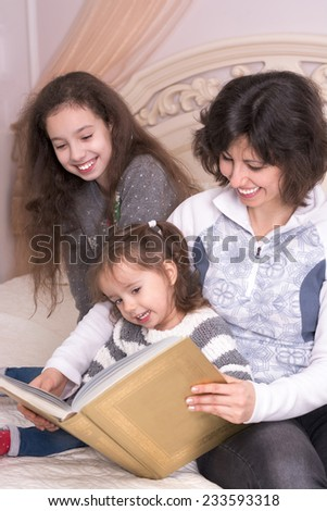 Mom reading a book with children. Little girl holding a big book - stock photo